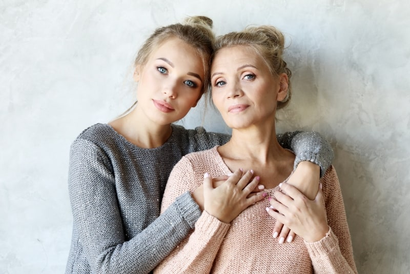 mother and daughter hugging while standing near wall
