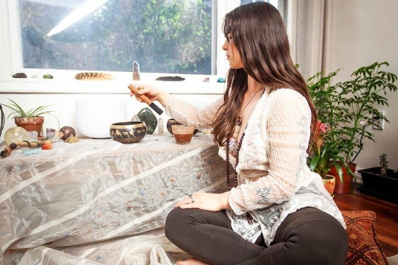 new age spiritual woman preparing incense while sitting near the windows