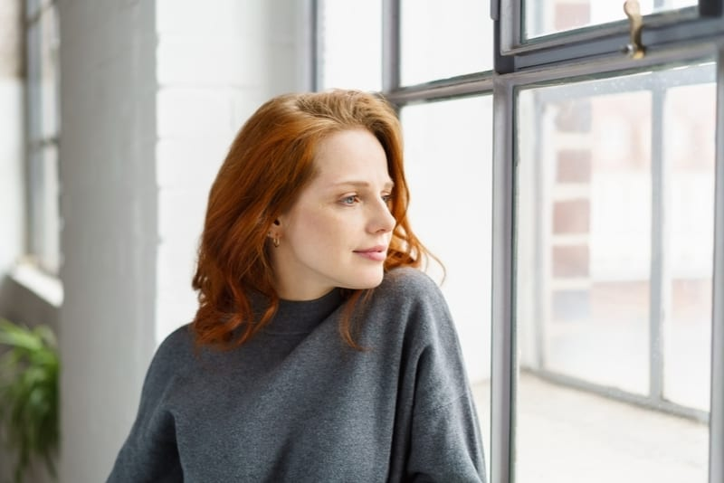 pensive attractive redhead woman standing near the windows