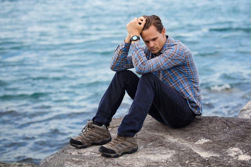 pensive man sitting on rock near a body of water