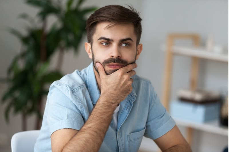 pensive man with moustache sit on office