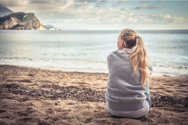 pensive woman sits near the sea looking far