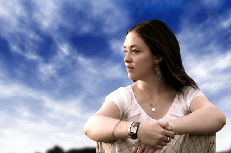 pensive woman sitting with blue sky as her background