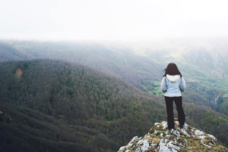 pensive woman standing at the peak of a mountain