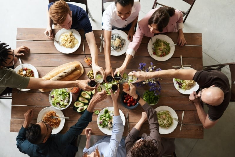 group of people making toast while sitting at table