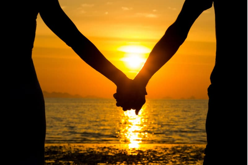 perfect scene valentines day in silhouette of couple's holding hand in the sunset facing the sea