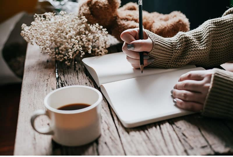 persons hand writing on a notebook with a cup of coffee near her