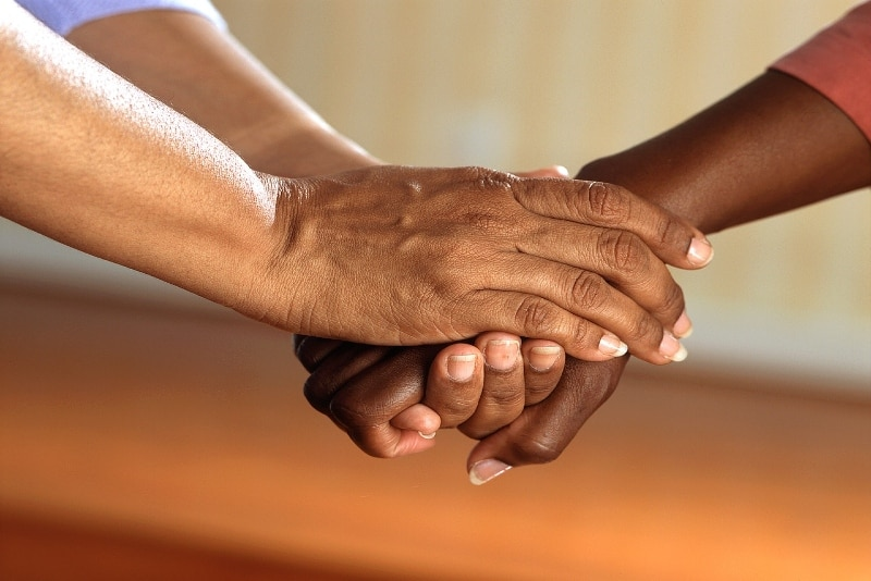 two persons holding hands indoor