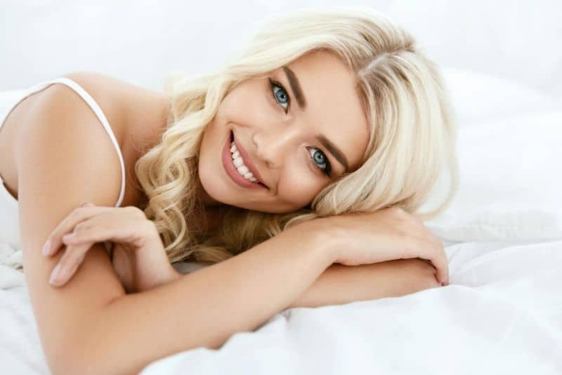 pretty blonde woman with blue eyes lying down on white bed and pillows