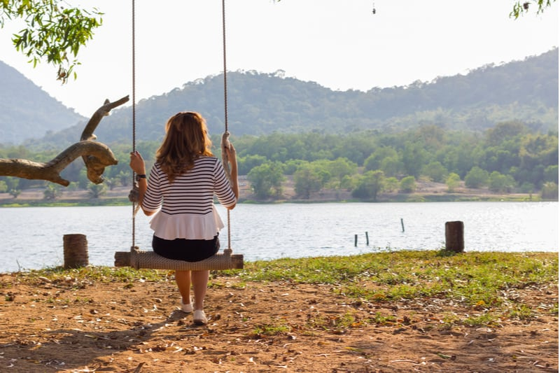rear view of a sad woman sitting on the swing near a lake