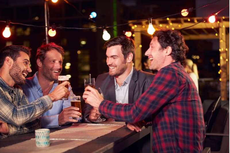 rooftop party of group of men drinking beers during the night