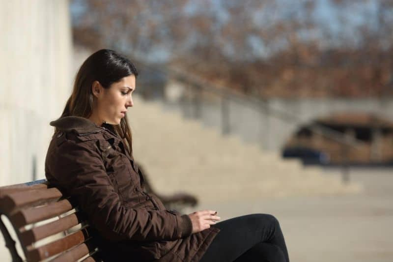 sad woman smoking and sitting on the outdoor bench