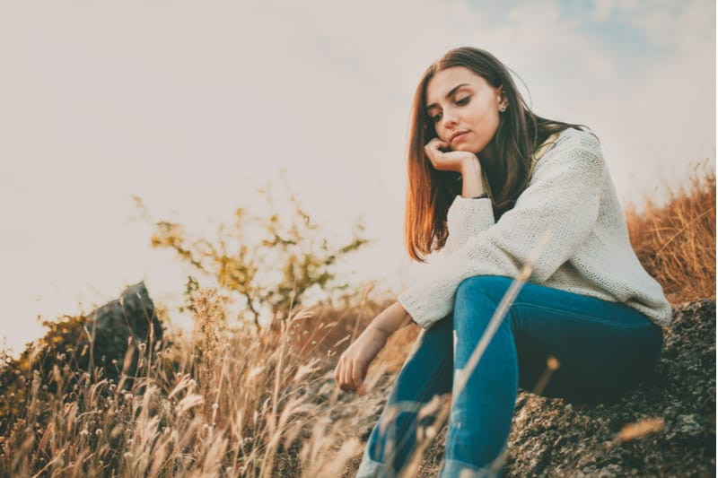 sad young lady sitting in the meadow deeply thinking