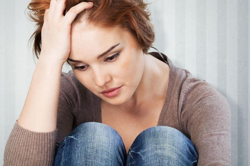 sad young woman holding her head while thinking