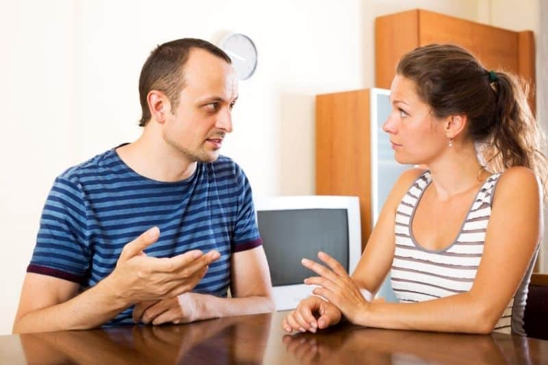 serious couple talking to each other in the table of their home