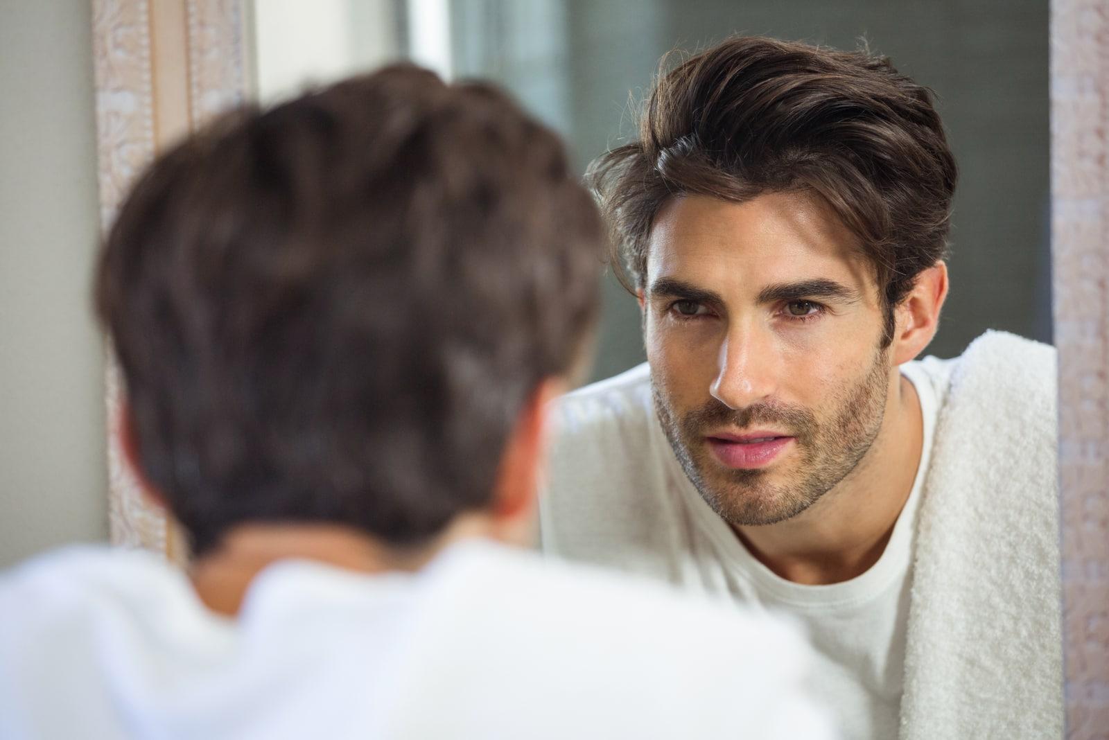 serious man looking at mirror