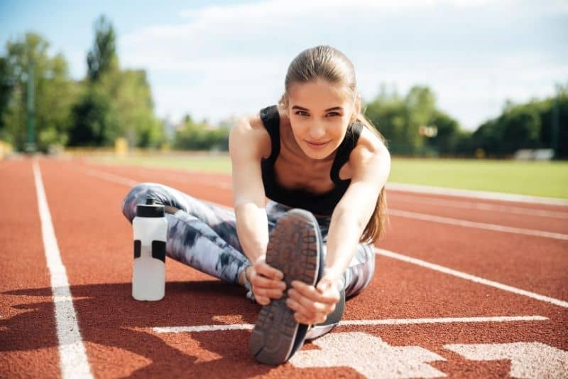 smiling woman athlete stretching in the middle of the tracking field