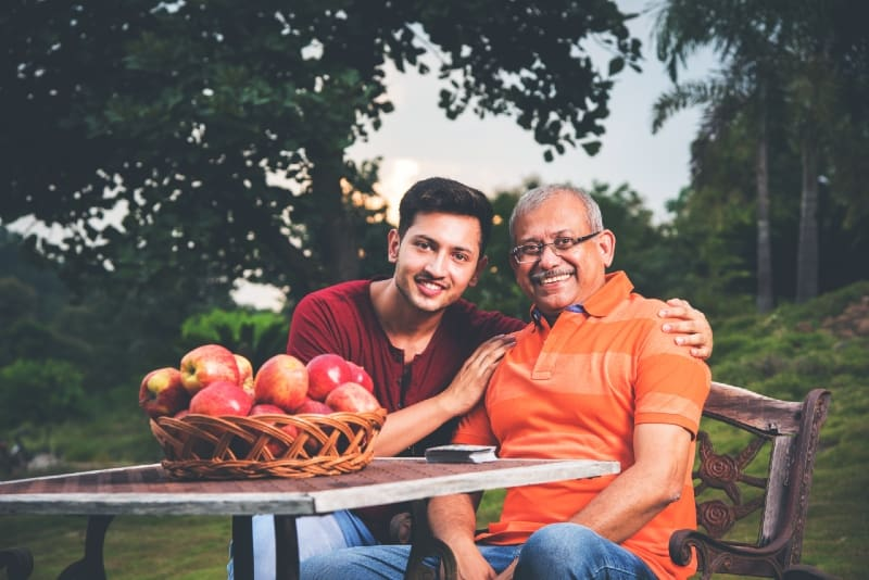 indian son hugging father while sitting at table