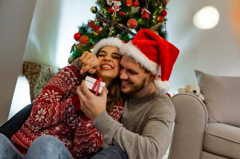 sweet couple opening gift inside home with a christmas tree behind them