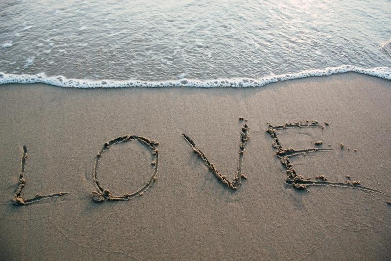 love text on seashore near sea
