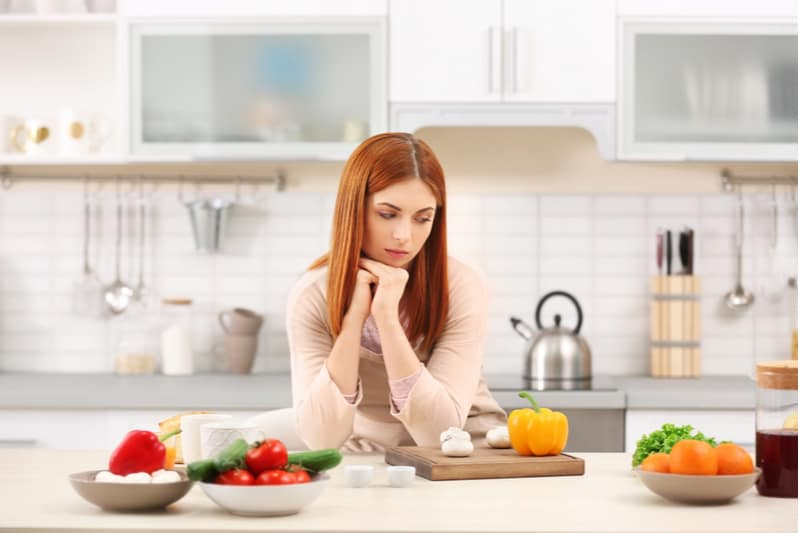 tired housewife cooking in the kitchen looking at the vegetables on the table