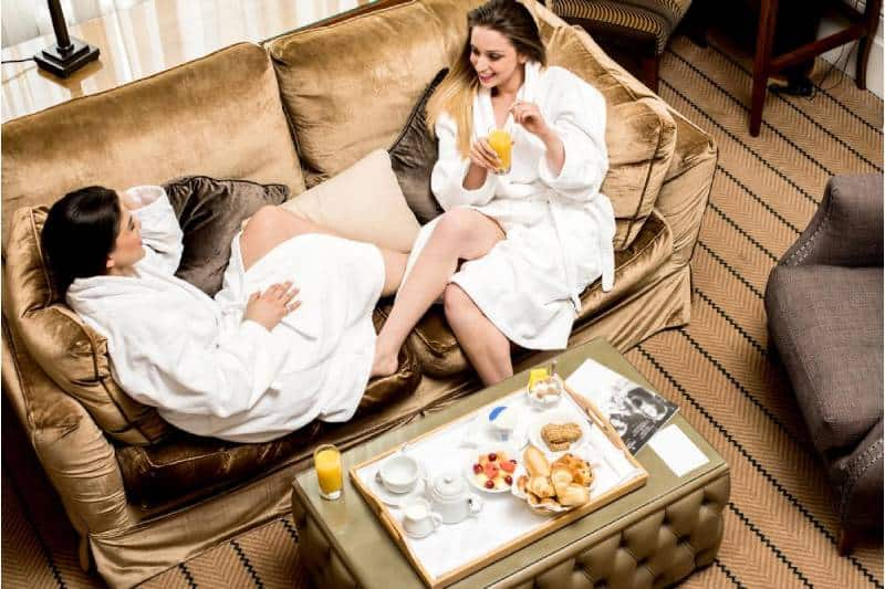 two friends in the spa eating foods while on their bath robe