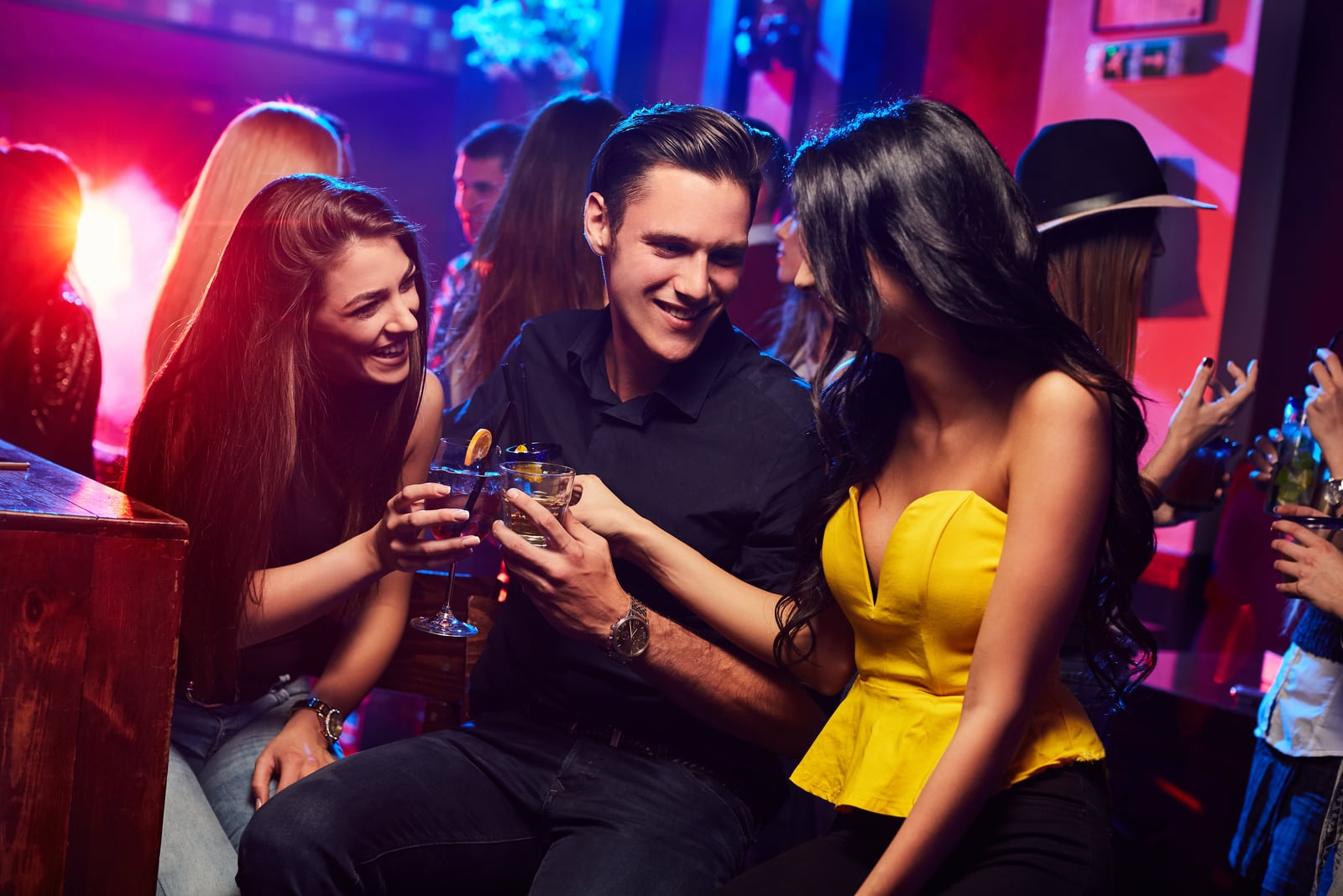 two girls with cocktails surrounding happy guy