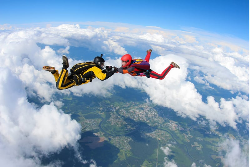 two people skydiving holding hands in air with clouds beneath them