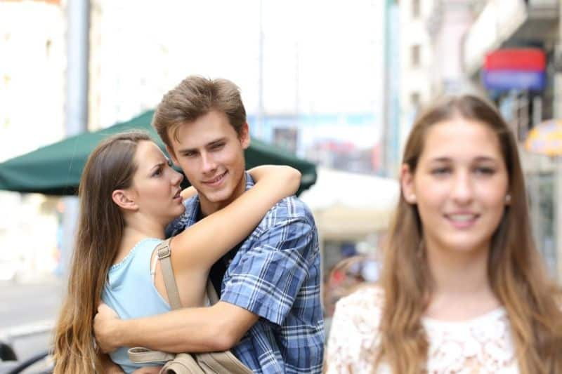 unfaithful boyfriend hugging girlfriend and looking at another woman in a distant