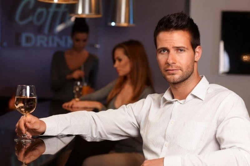unhappy man sitting on the bar near 2 women having drinks