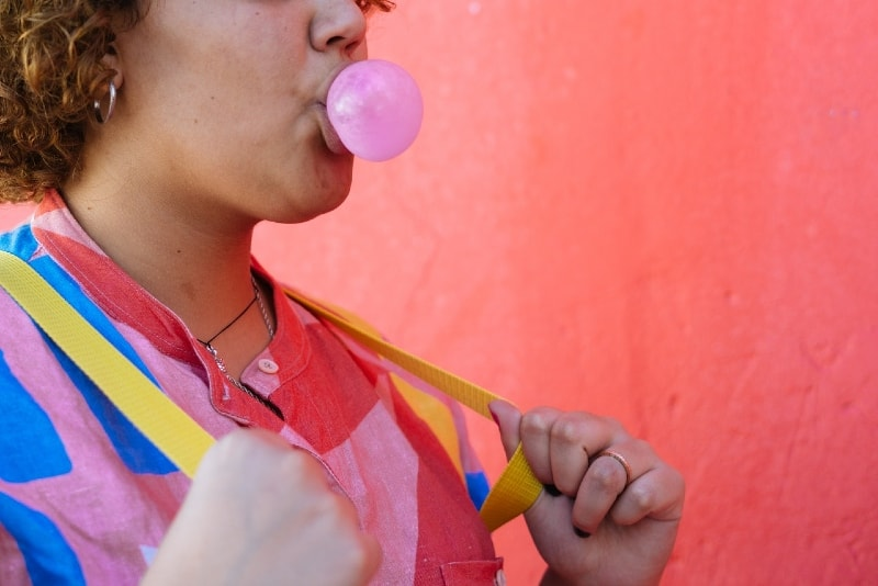 woman blowing gum bubble while standing near pink wall