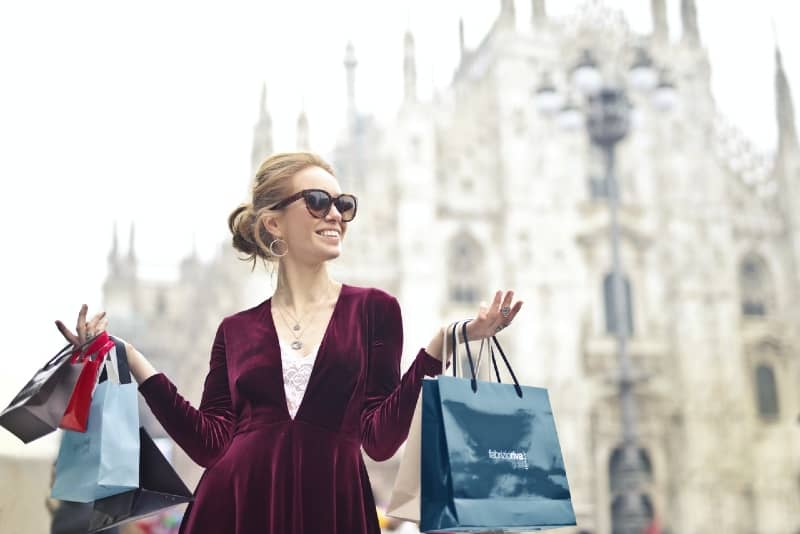woman with sunglasses carrying several paper bags