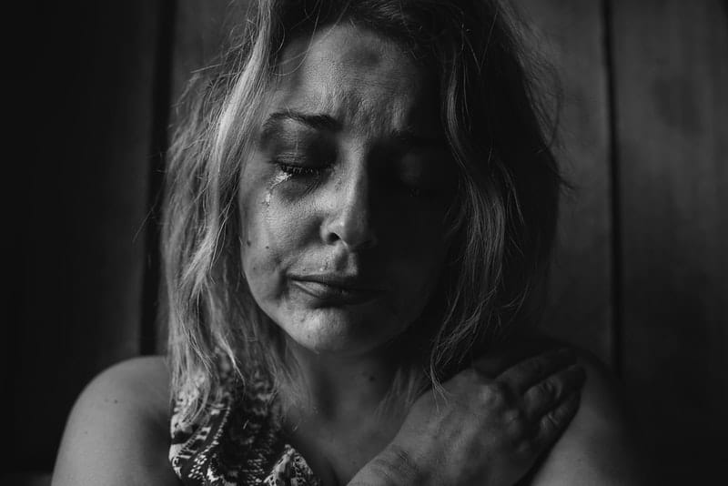 woman crying with bruises enbracing herself in grayscale theme