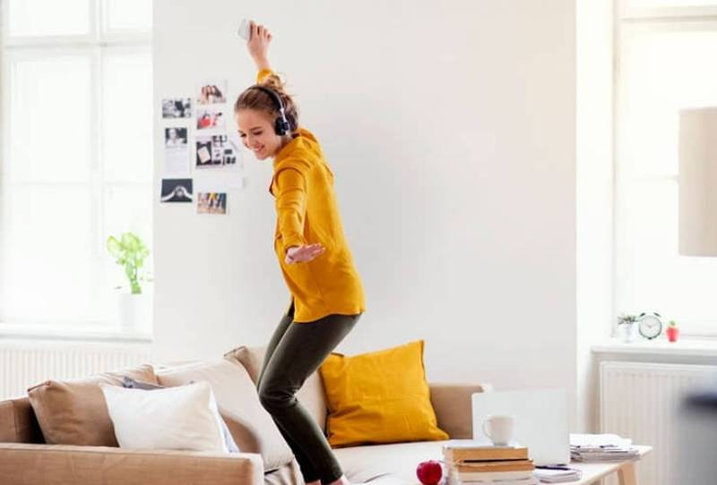 woman dances alone on top of the sofa inside living room using a headphone