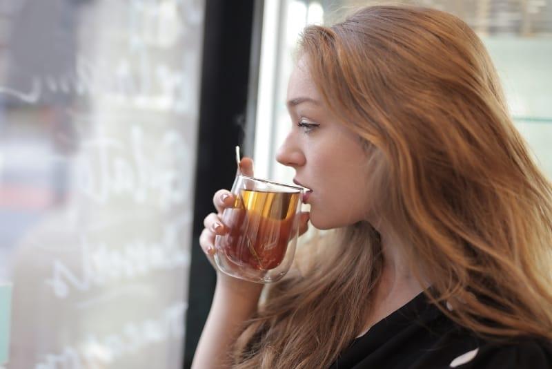 woman drinking tea while looking through window