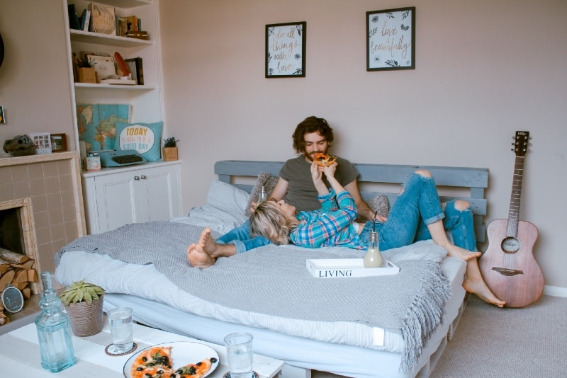 woman feeding man with pizza while lying on bed