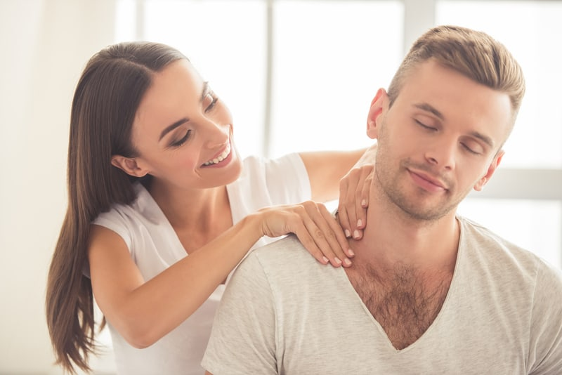 woman giving a massage on a man's shoulder while sitting