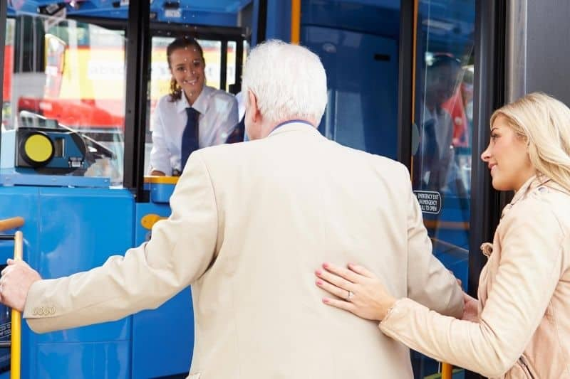 woman helping senior man getting in a public transportation