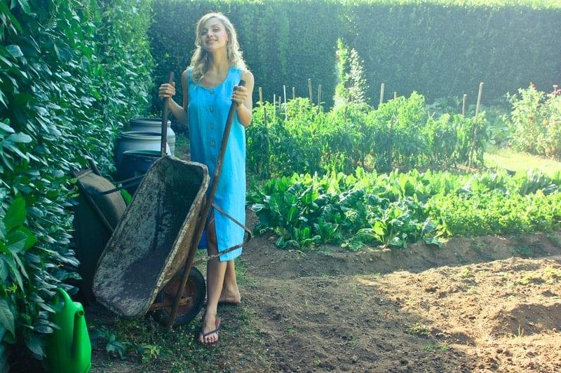 woman holding a wheelborrow smiling inside a big garden