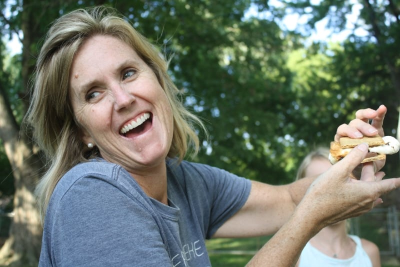 woman in gray t-shirt holding sandwich