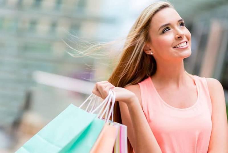 woman holding shopping bags wearing peach sleeveless shirt and looking upwards