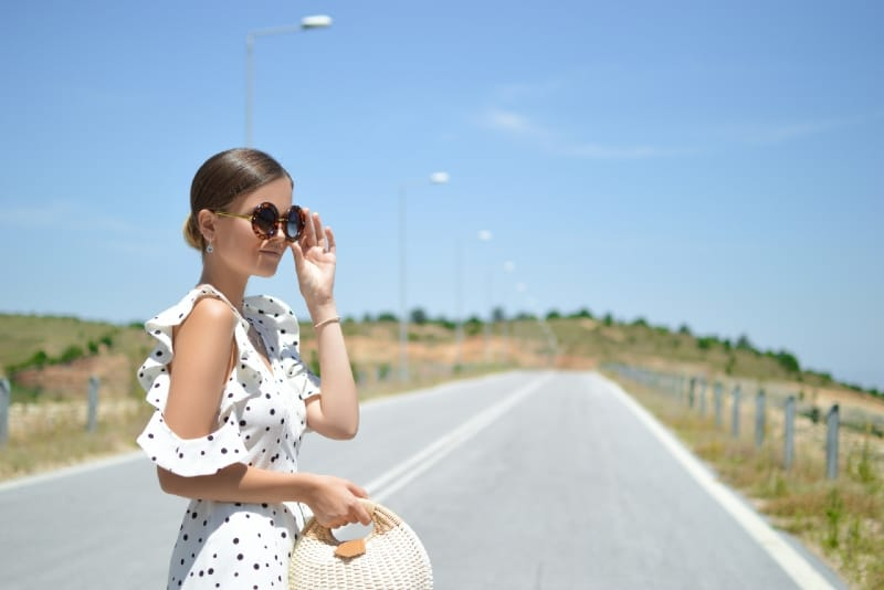 woman in ruffled polka dot dress holding sunglasses
