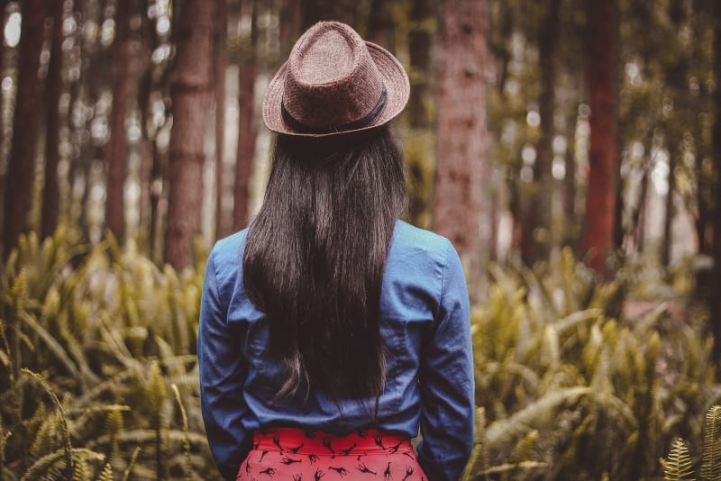 woman with hat standing in forest
