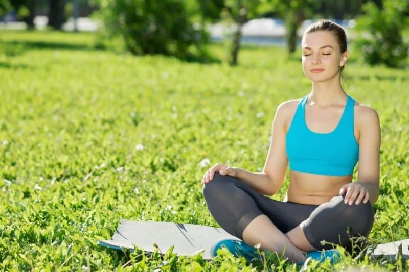 woman in park meditating wearing athletic wear