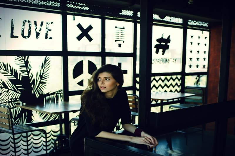 woman in black top leaning on desk