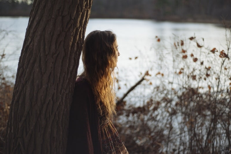 woman leaning on tree while standing near water