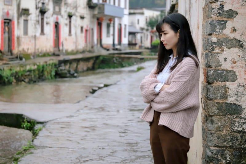 woman leaning on beige concrete wall