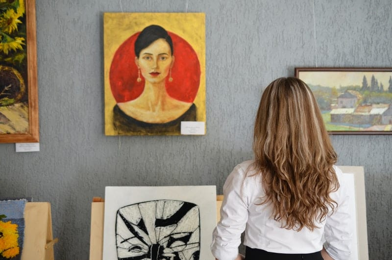 woman looking at art pieced hanged on the wall at an art gallery