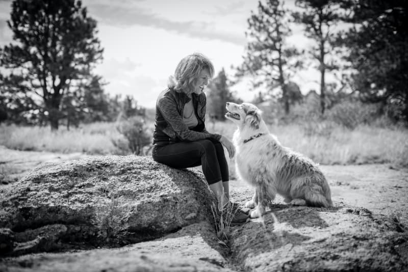 smiling woman looking at dog while sitting on rock