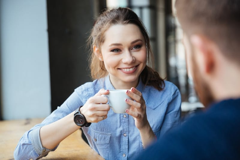 woman holding white mug while looking at man